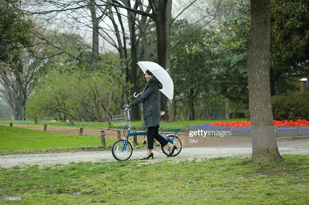 Young Woman Pushing the Bicycle in the Park, Side View  : Photo
