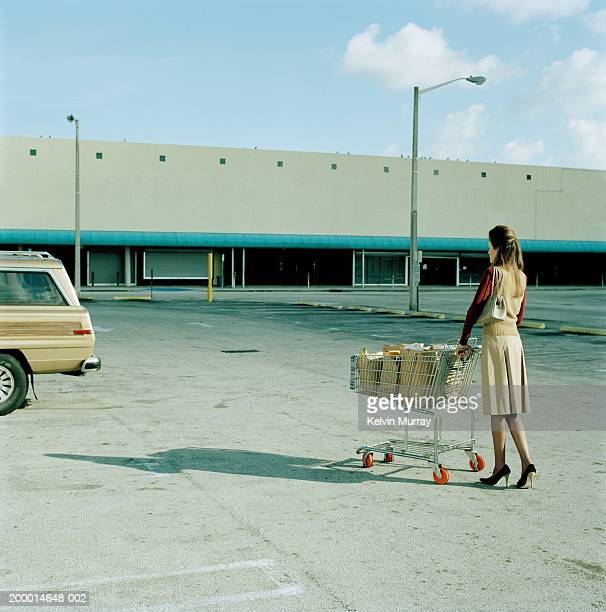 Young woman pushing trolly full of groceries in car park