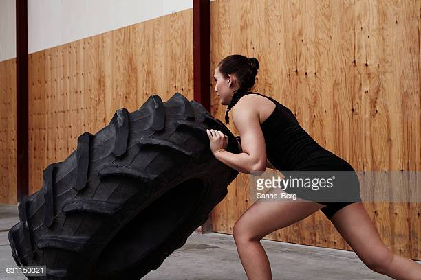 Young woman pushing truck tire in the gym