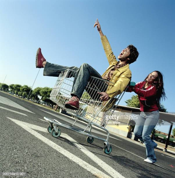 Young woman pushing young man in shopping trolley in carpark