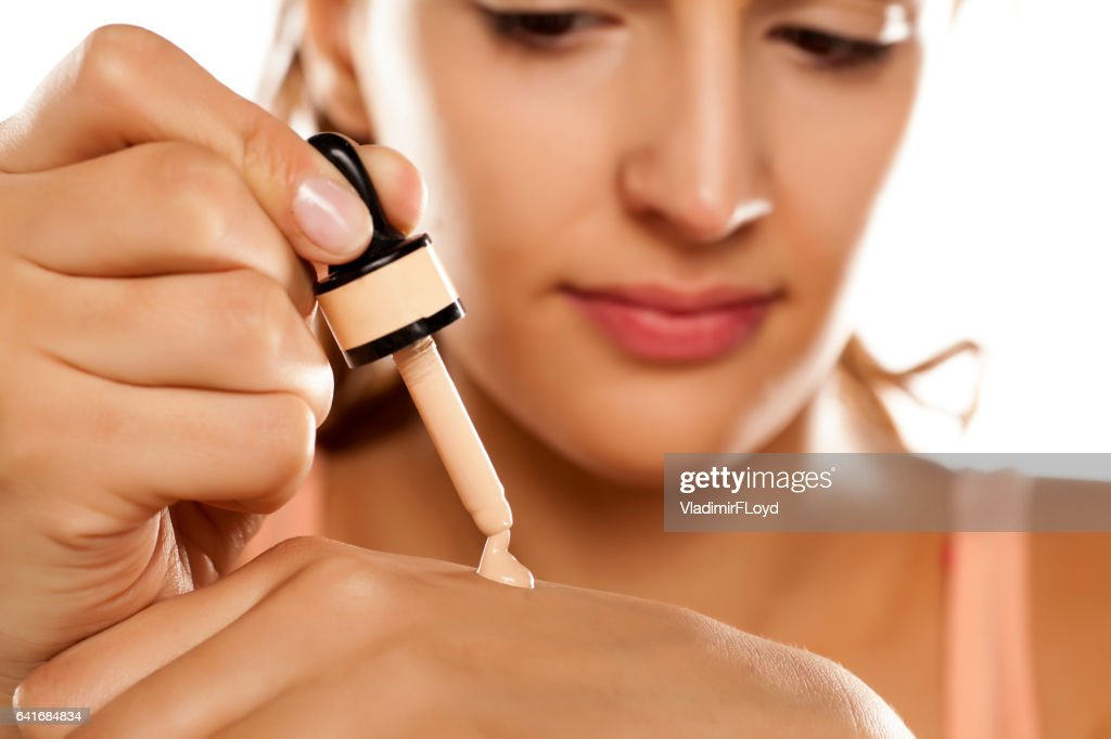young woman puts a liquid foundation on her palm : Stock Photo