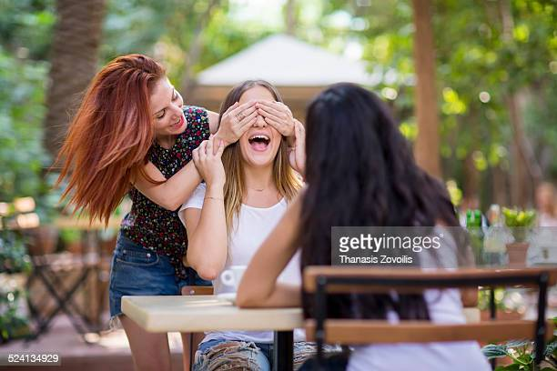 Young woman puts her hands over the eyes of friend