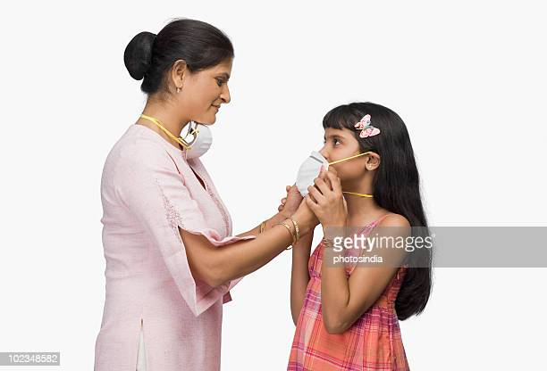 Young woman putting a pollution mask to her daughter