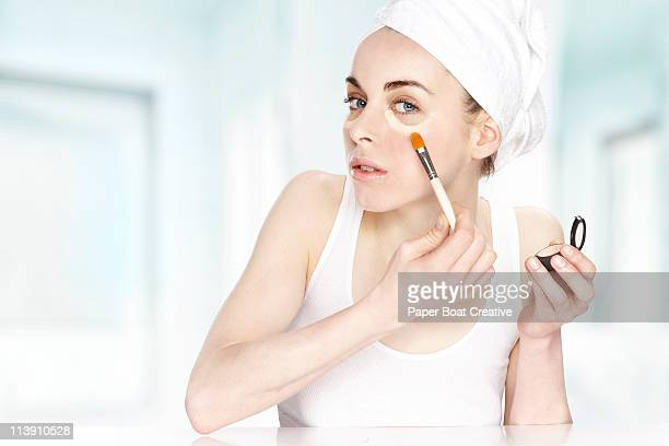 Young woman putting aconcealer under her eyes