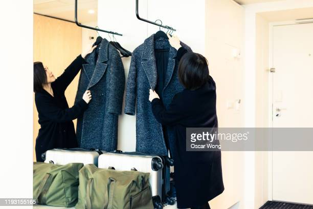 young woman putting coat on the hanger in hotel room - coat photos et images de collection