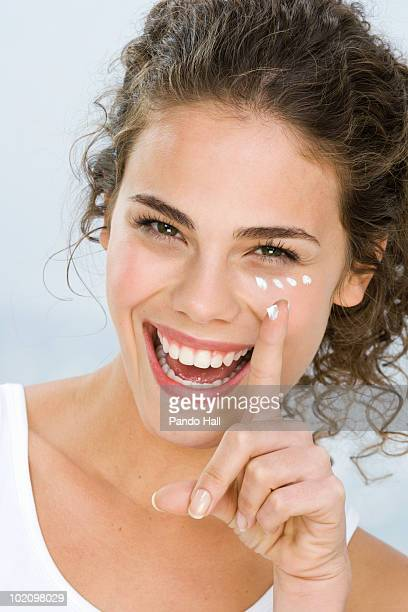 Young woman putting cream on face, laughing