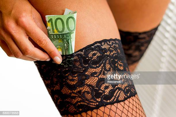 young woman putting euro note in her stocking - hoeren stockfoto's en -beelden