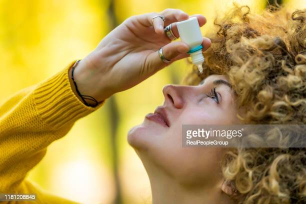 young woman putting eye drops - dry stock pictures, royalty-free photos & images