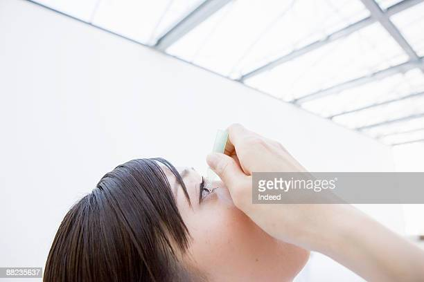 Young woman putting eye drops, side view