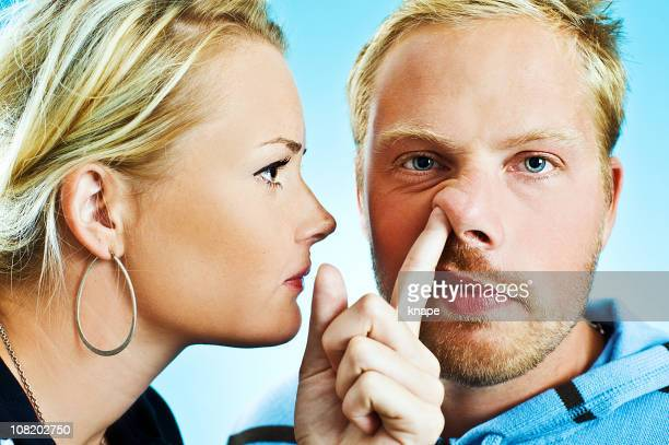 Young Woman Putting Finger up man's nose