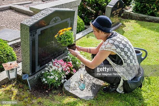 young woman putting flowers on tomb - friedhof stock-fotos und bilder