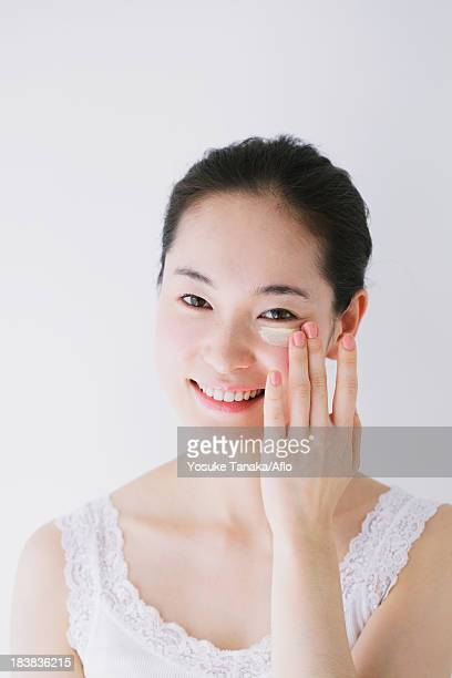 Young woman putting foundation cream