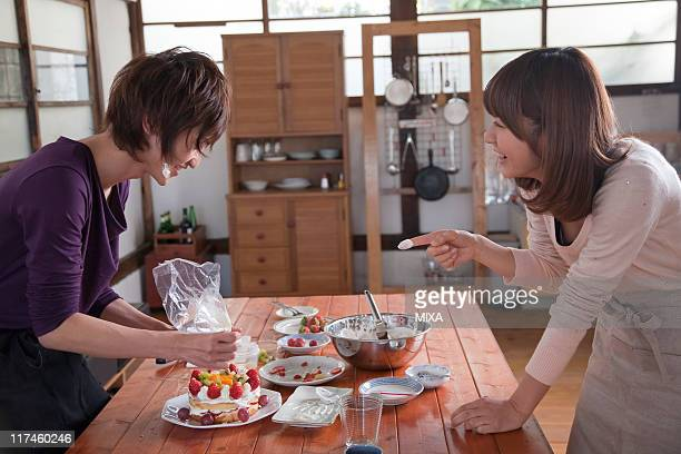 Young woman putting fresh cream on young man's face