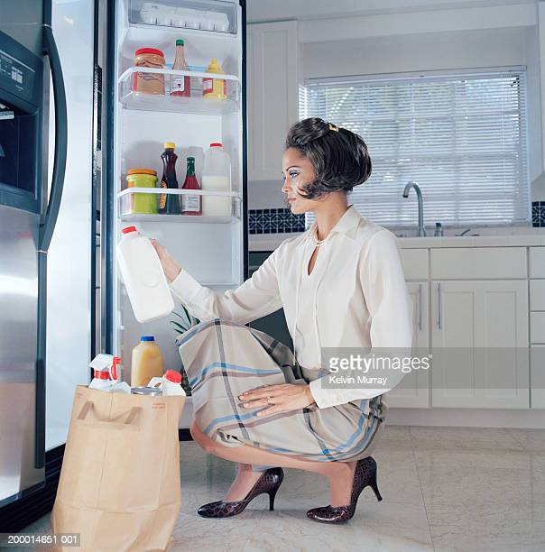 Young woman putting grocery shopping in refrigerator