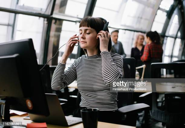 young woman putting headphones on while working in office - incidental people stock pictures, royalty-free photos & images