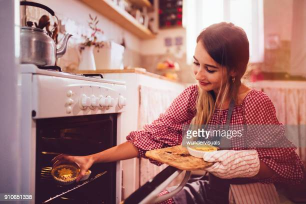 young woman putting homemade pies in kitchen oven for baking - old fashioned thanksgiving stock photos and pictures