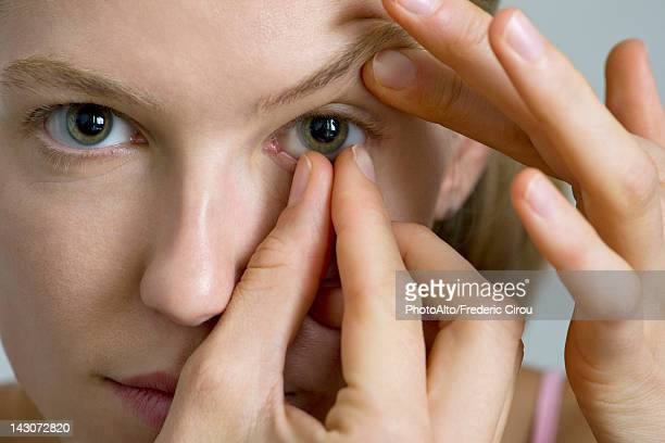 young woman putting in contact lens - contacts stock photos and pictures