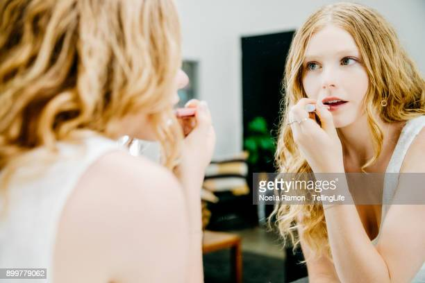 a young woman putting lipstick in front of a mirror - putting stock photos and pictures
