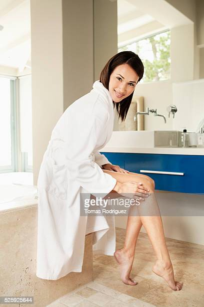 young woman putting lotion on legs - beautiful asian legs stock photos and pictures