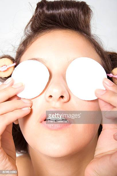Young woman putting makeup rounds on her eyes