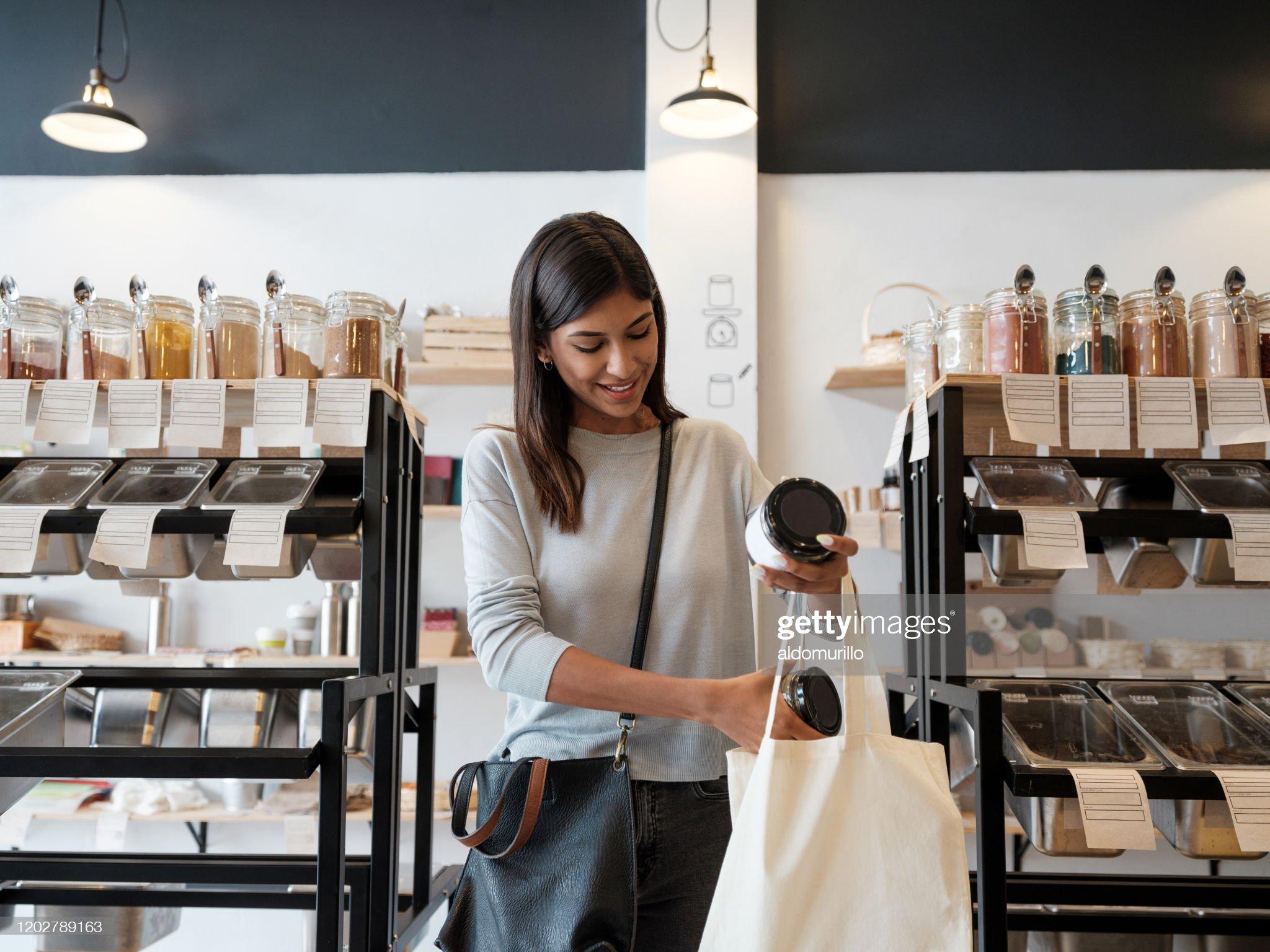 年輕女子把商品放在可重複使用的購物袋裡 : 圖庫照片