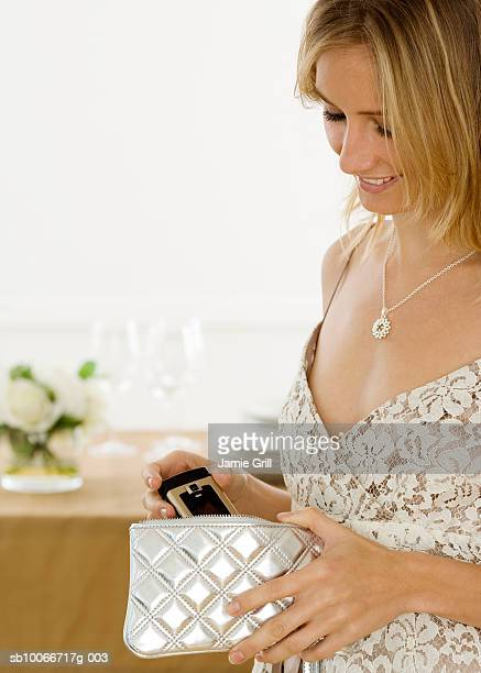 young woman putting mobile phone in purse, smiling (focus on foreground) - 位置付ける ストックフォトと画像
