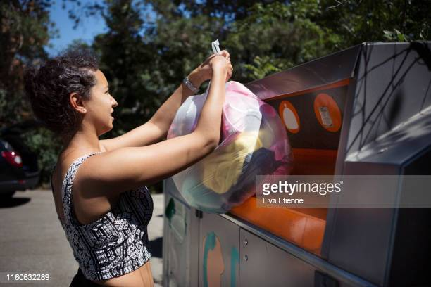 young woman putting old clothes into a bin at a recycling centre - donation box stock pictures, royalty-free photos & images