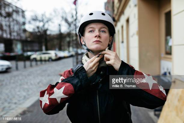 young woman putting on helmet before going out on bike - environmentalist stock pictures, royalty-free photos & images