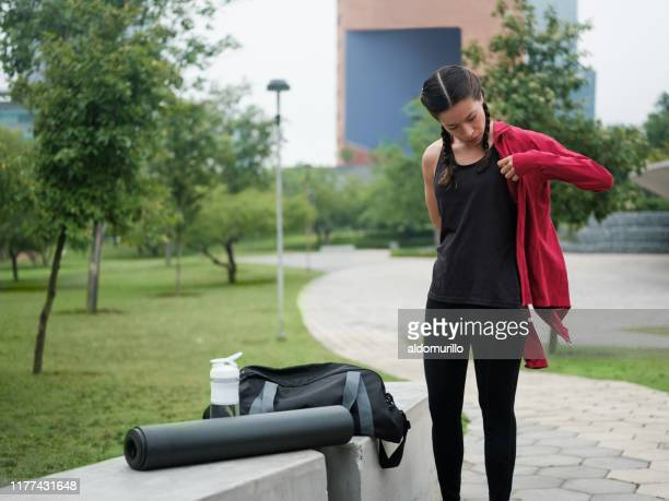 young woman putting on jacket outdoors - jacket stock pictures, royalty-free photos & images