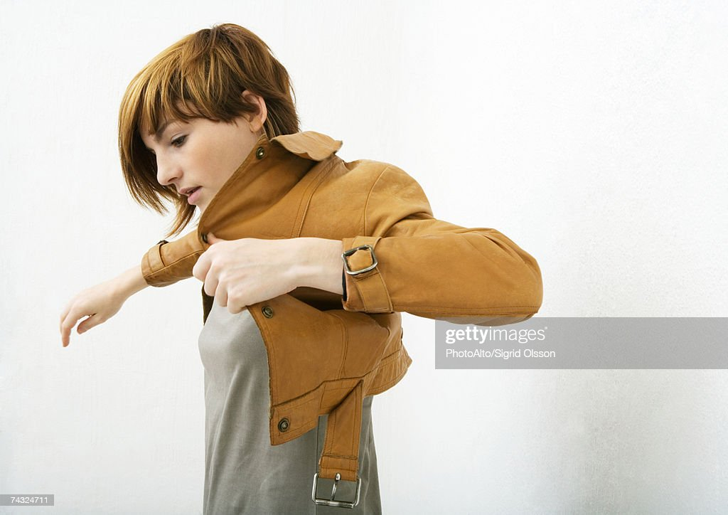 Young woman putting on jacket : Stock Photo