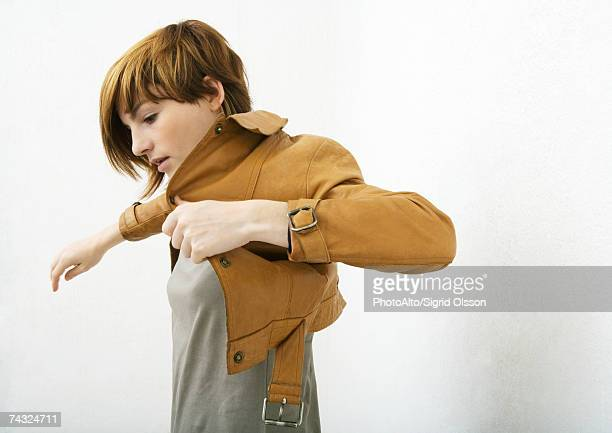 young woman putting on jacket - 着る ストックフォトと画像