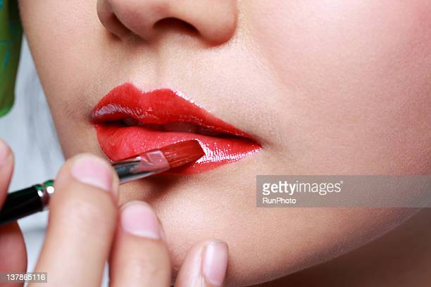 young woman putting on lipstick with brush