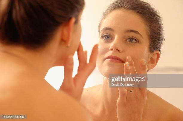 young woman putting on make up, reflection - putting stock photos and pictures