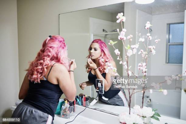 young woman putting on makeup in bathroom mirror while preparing for quinceanera - ceremony stock pictures, royalty-free photos & images