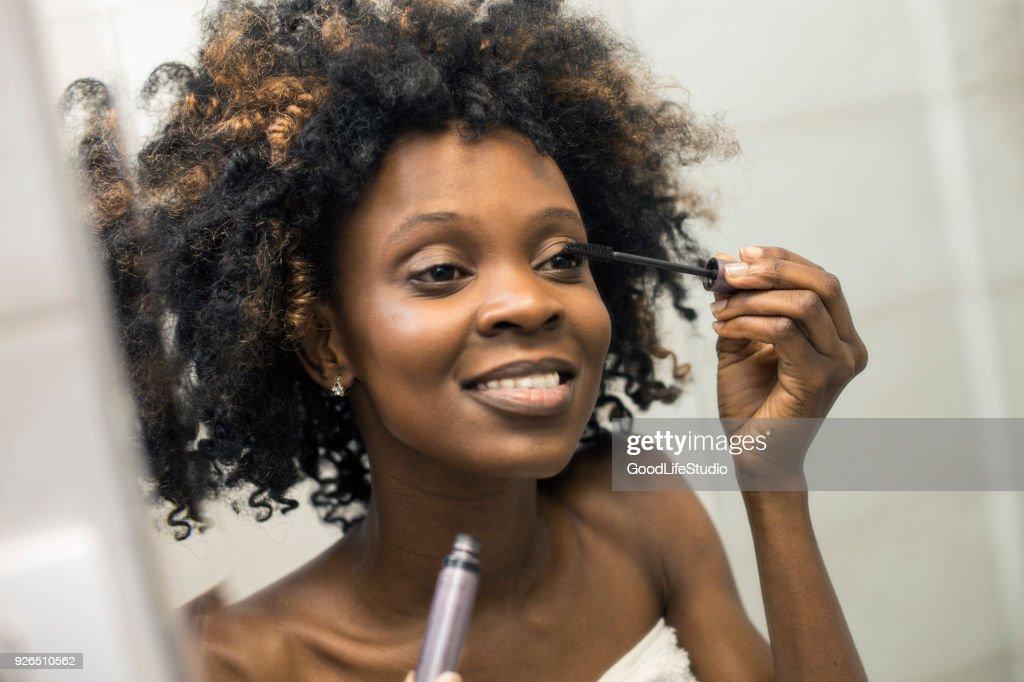 Young woman putting on mascara : Stock Photo
