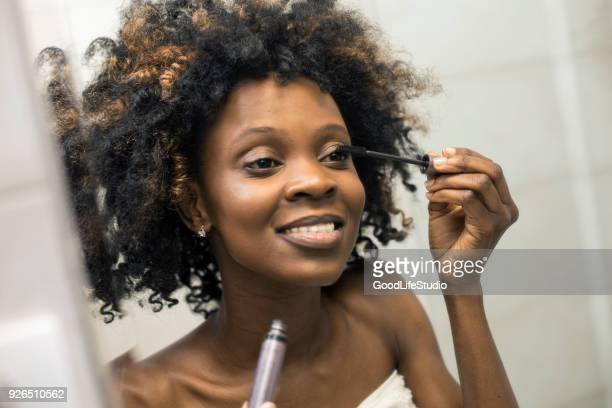 young woman putting on mascara - mascara stock pictures, royalty-free photos & images