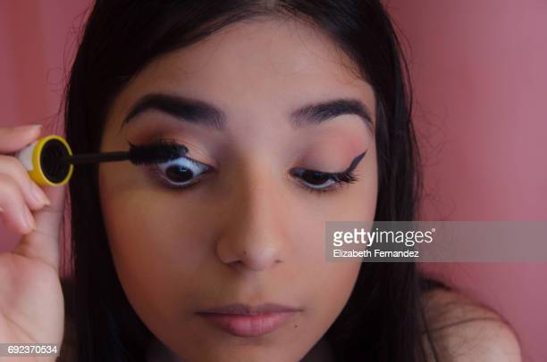 Young woman putting on mascara to her lashes.