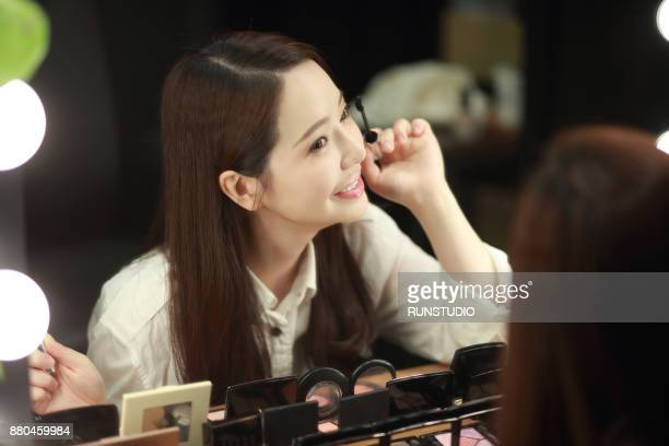 Young woman putting on mascara to her lashes