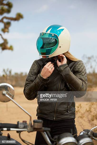 young woman putting on motorcycle helmet - crash helmet stock pictures, royalty-free photos & images