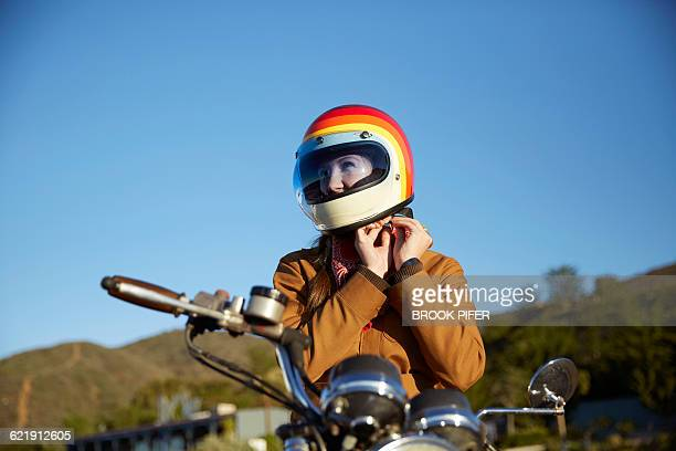 young woman putting on motorcycle helmet - sportschutzhelm stock-fotos und bilder