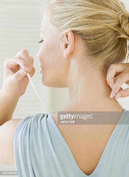 Young Woman putting on pearl necklace