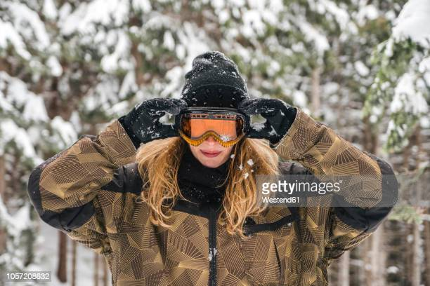 young woman putting on ski goggles in winter forest - ski goggles stock pictures, royalty-free photos & images