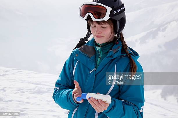 Young woman putting on sunscreen in the snow