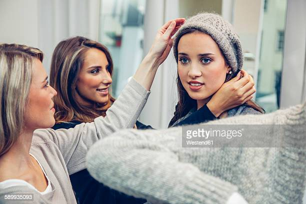 Young woman putting on woolly hat in a boutique assisted by two women