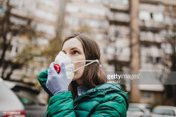 young woman putting protection mask from virus - immune system stock pictures, royalty-free photos & images
