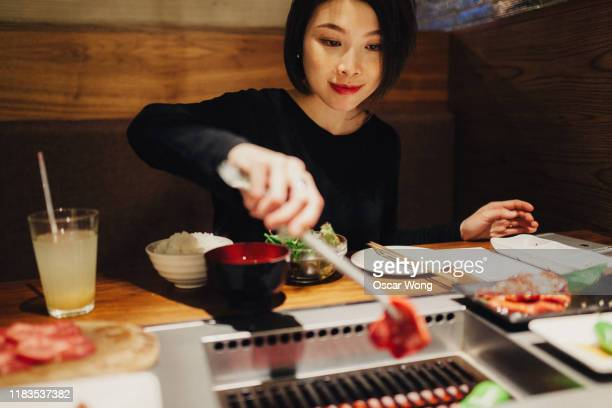 young woman putting raw beef on grill - 副菜 ストックフォトと画像