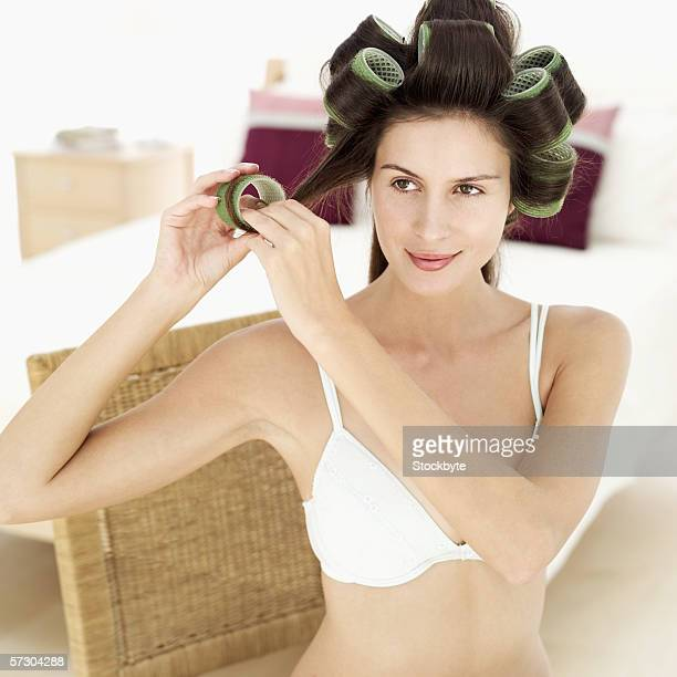 Young woman putting rollers on her hair