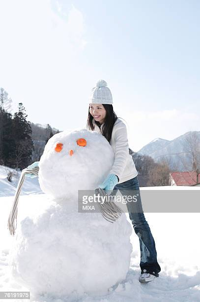 Young woman putting scarf on snowman
