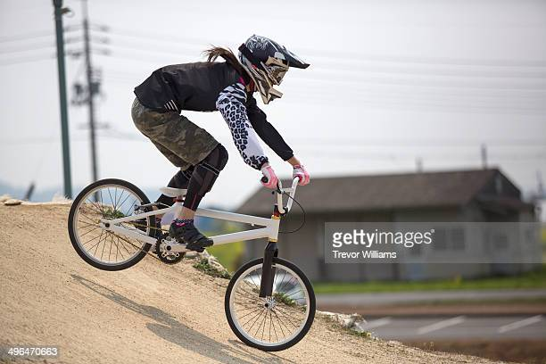 a young woman racing a bmx bike on a track - bmx cycling stock pictures, royalty-free photos & images