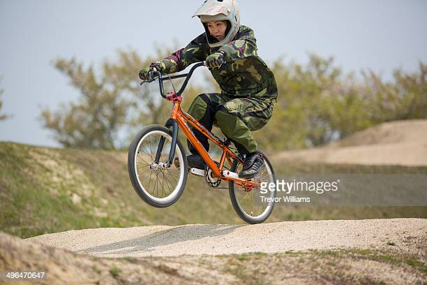A young woman racing on a BMX bike